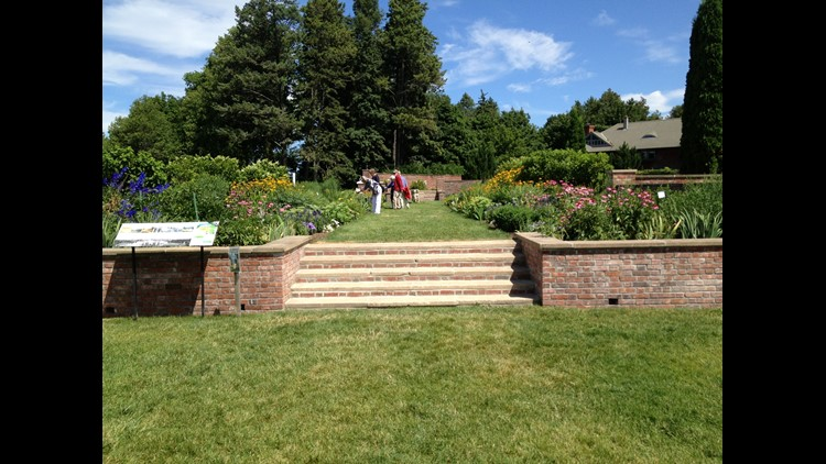 Visitors stop to smell the flowers in the formal gardens at Shelburne Farms.