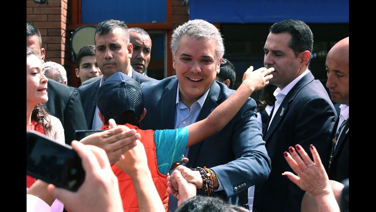 Presidential candidate Ivan Duque greets his supporters as he arrives at his polling station for the second round of presidential elections, in Bogota, Colombia, on June 17, 2018.