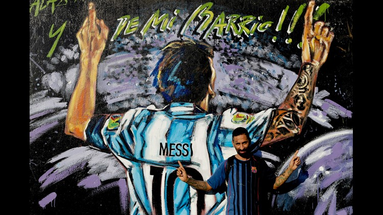 """In this April 18, 2018 photo, Alejandro Daniel Fernandez poses for a photo by a mural of his childhood friend, Lionel Messi, that reads in Spanish """"From my neighborhood!"""" in La Bajada, Rosario, Argentina. Fernandez said Messi's family had always helped hi"""
