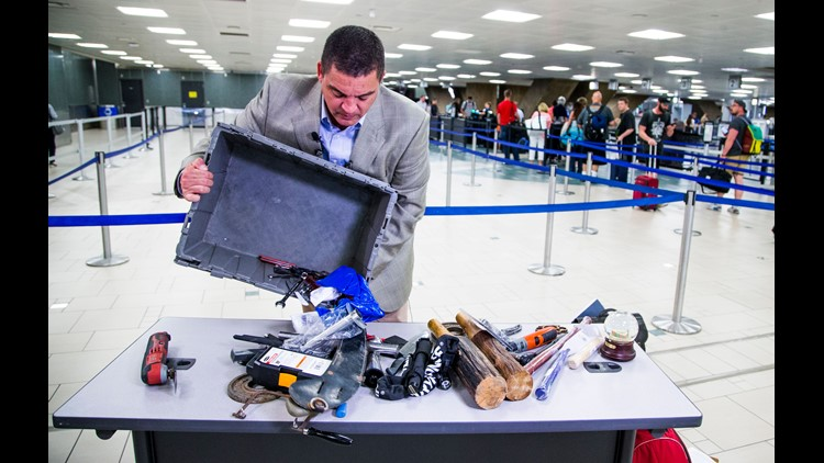 Nico Melendez, a spokesman for the Transportation Security Administration, shows items not allowed as carry ons and then left behind at security checkpoints at Sky Harbor International Airport in the previous 48 hours.