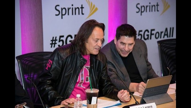 T-Mobile CEO John Legere (left) and Sprint Executive Chairman Marcelo Claure are seen at the press conference to announce their companies' merger.