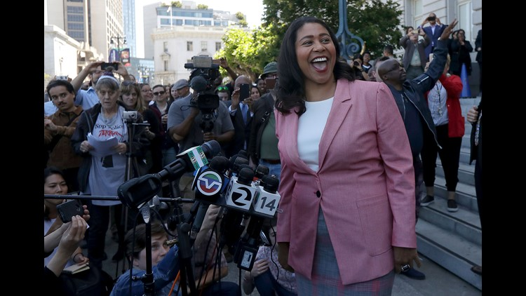 London Breed smiles toward supporters before speaking to reporters outside of City Hall in San Francisco.