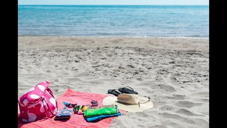 Picture of a bech and ocean with beach blanket.