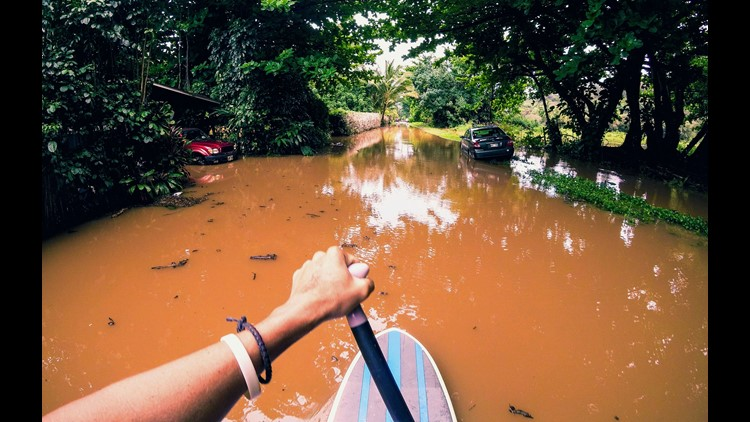 This April 15, 2018, photo provided by Kauai resident James Hennessy shows the view as he maneuvers a stand-up paddleboard along his flooded street in Haena, Hawaii.