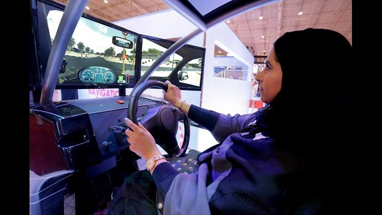 A women sits in a driving simulator during a car show only for women in Riyadh, Saudi Arabia,
