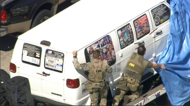 This frame grab from video provided by WPLG-TV shows FBI agents covering a van after the tarp fell off as it was transported from Plantation, Fla., on Friday, Oct. 26, 2018, that federal agents and police officers have been examining in connection with pa