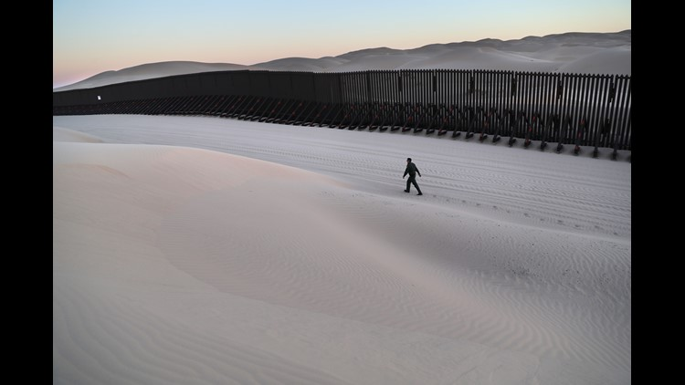 "A U.S. Border Patrol agent walks along the U.S.-Mexico border at the Imperial Sand Dunes on Nov. 17, 2016 near Felicity, Calif. The 15-foot border fence, also known as the ""floating fence,"" sits atop the dunes and moves with the shifting sands. Border Pat"