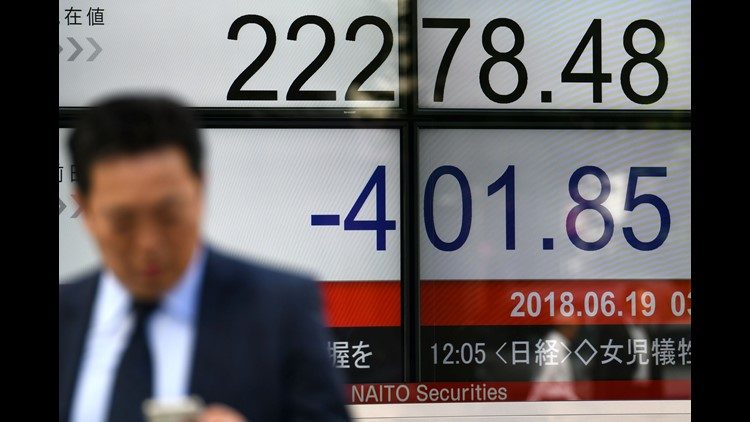 A pedestrian walks past a stock indicator displaying the closing rate of the Tokyo Stock Exchange in Tokyo on June 19, 2018.