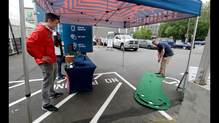 Amazon worker Tony Biallas, left, watches as a customer plays a golf game at an Amazon Treasure Truck in Seattle. The Treasure Truck is a quirky way for the online retailer to connect with shoppers in person, expand its physical presence and promote itsel