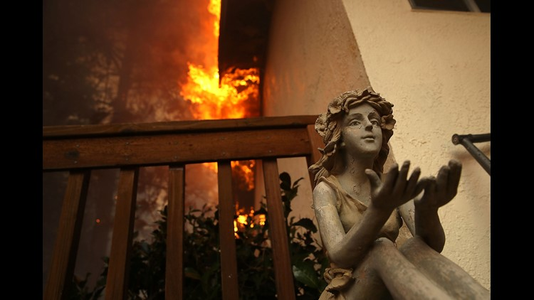 A statue sits on the deck of a burning home as the Camp Fire moves through the area on November 8, 2018 in Paradise, California. Fueled by high winds and low humidity, the rapidly spreading Camp Fire has ripped through the town of Paradise and has quickly