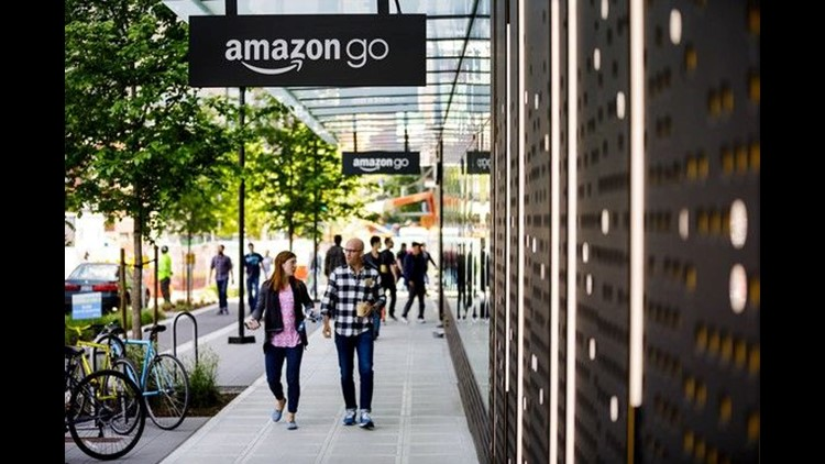 A man and a woman walk under the Amazon Go store signs in Seattle.