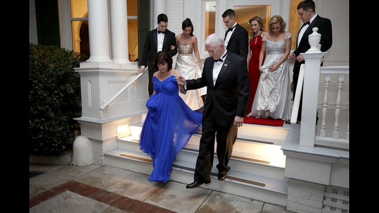 Vice President Mike Pence helps wife, Karen, down the steps of the front porch of the vice presidential residence at the U.S Naval Observatory before heading to the inaugural balls  in Washington, D.C., with their children on Jan. 20, 2017.