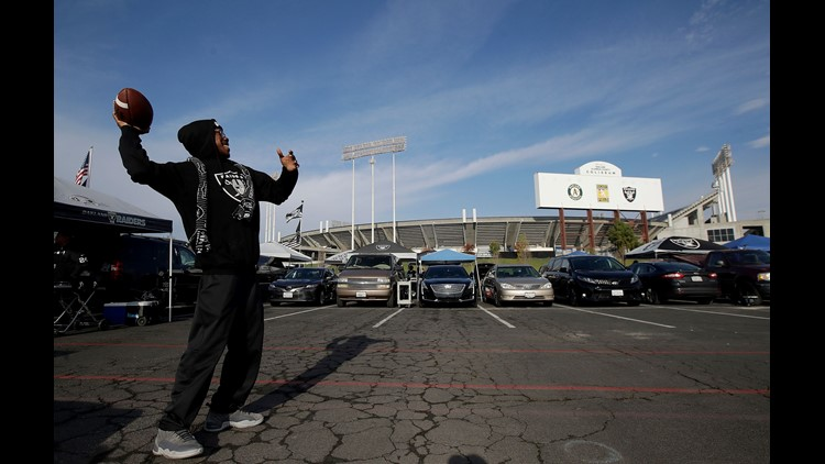 In this Dec. 9, 2018, file photo, a fan throws a football as people tailgate outside Oakland Coliseum before an NFL football game between the Oakland Raiders and the Pittsburgh Steelers in Oakland, Calif.