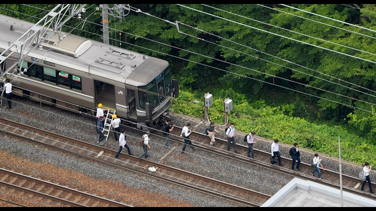 Passengers walk on railroad as train service was suspended following an earthquake in Takatsuki, Osaka, Japan, on Monday.