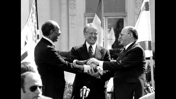 Egyptian President Anwar Sadat, left, U.S. President Jimmy Carter, center,  and Israeli Prime Minister Menachem Begin clasp hands on the north lawn of the White House after signing the peace treaty between Egypt and Israel on March 26, 1979. Sadat and Beg