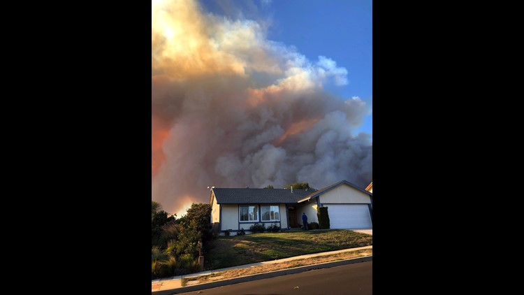 Plumes of smoke loom in the sky several miles away, seen behind a home in Thousand Oaks, Calif., as a wind-driven wildfire known as the Hill fire threatens the area late Thursday afternoon, Nov. 4, 2018. This is a few miles from the scene of Wednesday's m