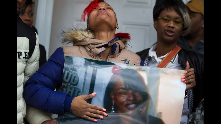 LaTonya Jones, the daughter of Bettie Jones holds a picture of her  mother during a vigil outside her home on December 27, 2015 in Chicago, Illinois. Bettie Jones was shot and killed yesterday at the front door of her home by police responding to a domest