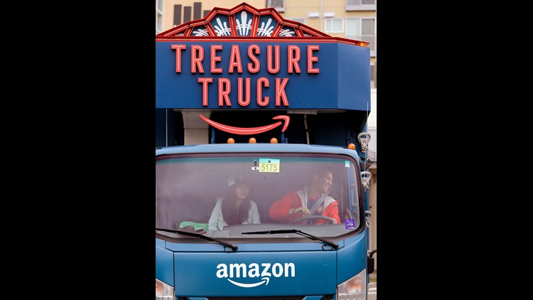 In this May 24, 2018, photo Amazon worker Tony Biallas, right, backs-up an Amazon Treasure Truck into a parking spot as intern Mavis Rong rides shotgun in Seattle. The Treasure Truck is a quirky way for the online retailer to connect with shoppers in pers