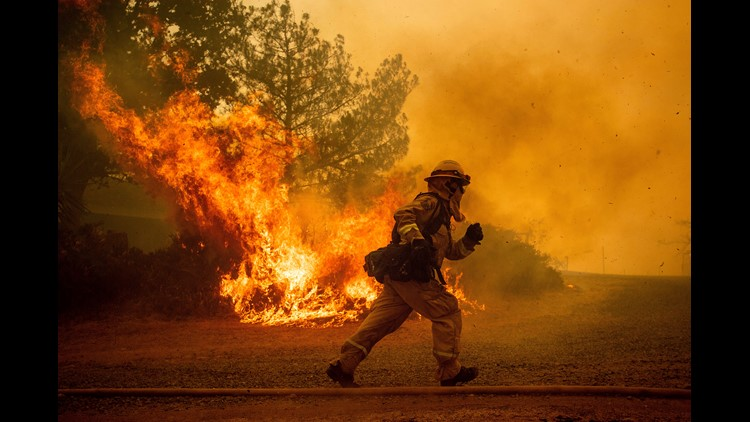 A firefighter runs while trying to save a home as a wildfire tears through Lakeport, Calif. The residence eventually burned.