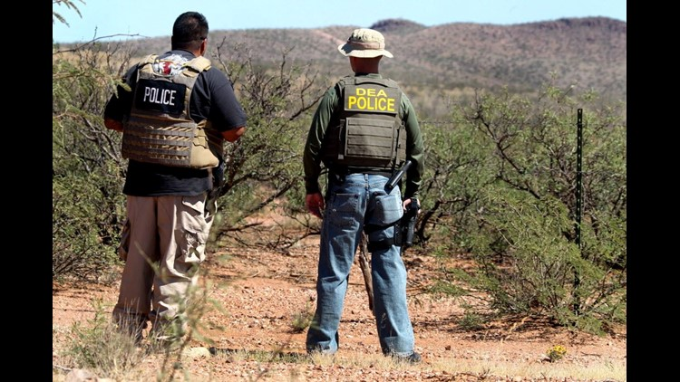 Det. Bill Silva, left, with the Bisbee Police Department and an unnamed agent with the Drug Enforcement Administration patrol a fence line east of Naco, Ariz., in 2012.