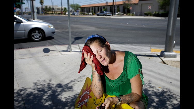 Amanda Ouellet wipes her face with a cold wet towel to cool off while working outside holding an advertising sign Tuesday, July 1, 2014, in Las Vegas. Temperatures will soar above 95 degrees for much of the central U.S. this weekend.