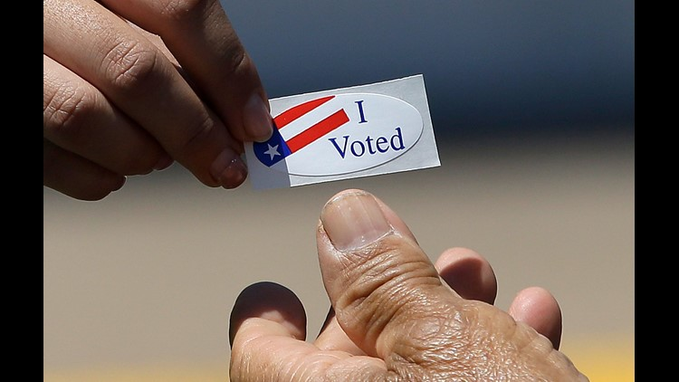 "Kimberlee Weaver, left, an election worker for the Sacramento County Registrar of Voters, hands an ""I Voted"" sticker to a voter during the state's primary elections  in Sacramento, Calif."