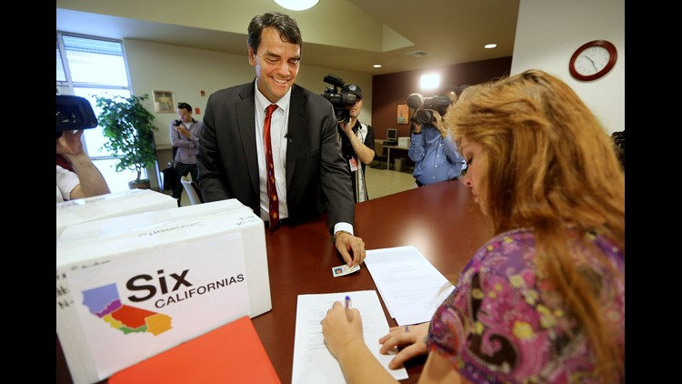 Silicon Valley venture capitalist Tim Draper presents his driver's license for identification purposes to Heather Ditty, elections  manager for the Sacramento County Registrar of Voters, as he turns in boxes of petitions for a ballot initiative asking vot
