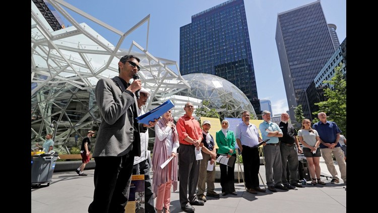 Shankar Narayan, legislative director of the ACLU of Washington, left, speaks at a news conference outside Amazon headquarters, Monday, June 18, 2018, in Seattle. Representatives of community-based organizations urged Amazon to stop selling its face surve