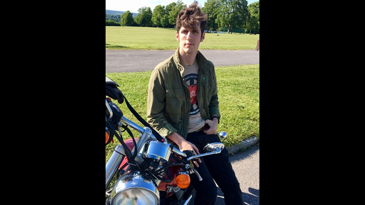 """In this June 15, 2018, photo, West Point graduate Spenser Rapone leans on his motorcycle at a park in Watertown, N.Y. As of Monday, June 18, Rapone will be out of the Army with an """"other than honorable"""" discharge for """"conduct unbecoming of an officer,"""" in"""
