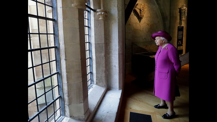 Queen Elizabeth II looks through a window at the view as she walks through The Queen's Diamond Jubilee Galleries at Westminster Abbey in London