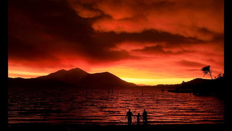 Evacuees from Lucerne, from left, Ken Bennett with Ember Reynolds, 8, and Lisa Reynolds watch the sunset as smoke from the Ranch Fire rises into the sky at Austin Park Beach in California's Clearlake with Mount Konocti in the background.
