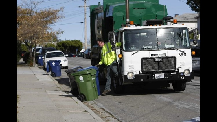 A Waste Management employee collects garbage in Castro Valley, Calif., Friday, Dec. 18, 2009.