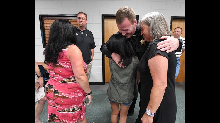 Anderson County Sheriff Chad McBride hugs Jordan Reyes and her mother Kim Friday, June 8, 2018 at the Anderson School District 5 administrative offices after a press conference to release the video showing where Jordan was narrowly missed by a Anderson sh