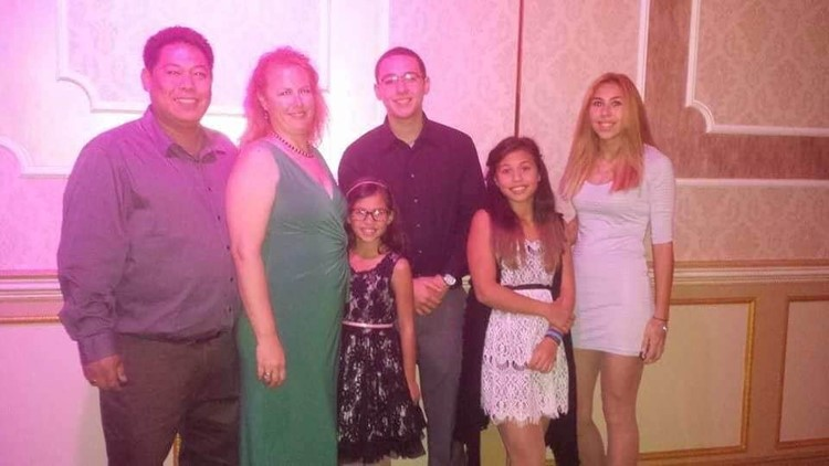 Cloyd Edralin, left, a green card holder who has lived in the U.S. for 30 years, is pictured next to his wife, Brandi Davison-Edralin, and their four children ages 11 to 22. Edralin was detained by immigration officers Monday morning over an 11-year-old f