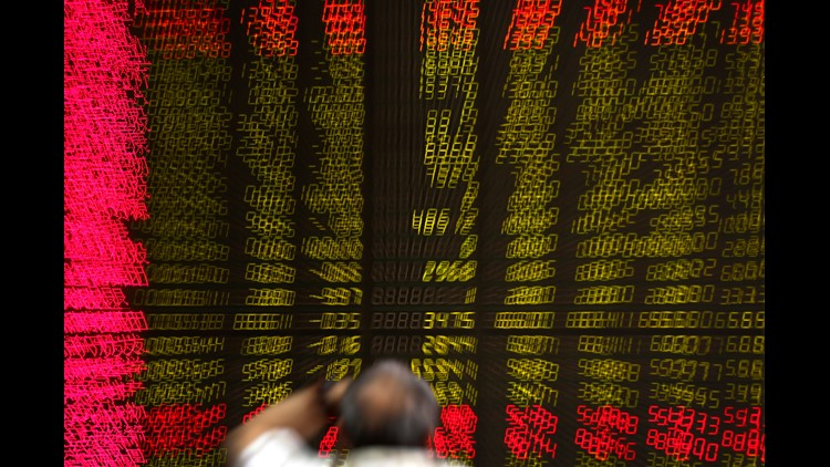 In a photo made with a pulled-zoom effect, a man watches stock prices at a brokerage house in Beijing, Tuesday, June 12, 2018.