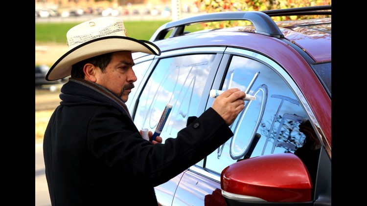 "Jose Vargas, 56, draws ""vote"" and ""vota"" on his Mazda SUV windows on  Nov. 6, 2018, in Dodge City, Kansas while waiting to give rides to the polls to midterm election voters who needed transportation or accidentally showed up at the wrong polling place."