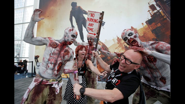 Polish developers Adrian Kornecki and Malgorzata Mitrega with Dying Light 2 interact with zombie game characters.