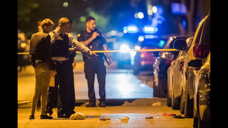 In thisJune 14, 2018, photo, Chicago police officers investigate the scene where two people were shot. A 12-year-old Michigan girl spending the summer in Chicago was fatally shot at the scene, hours after attending a cousin's eighth-grade graduation. Fami