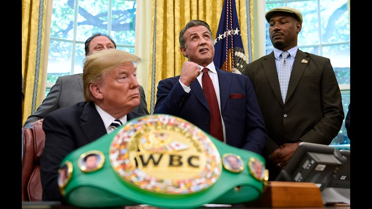 President Trump, Sylvester Stallone, and heavyweight champion boxer Lennox Lewis, right, watch in the Oval Office where Trump granted a posthumous pardon to Jack Johnson, boxing's first black heavyweight champion.
