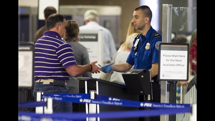 A TSA officer checks the credentials of a traveler at Phoenix Sky Harbor International Airport.