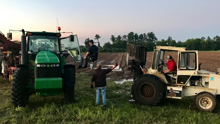 Mark Edling is lifted by fork lift into the cab of a John Deere tractor