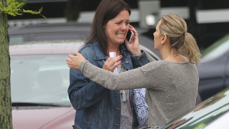 Two people react outside East Brook Middle School after a horrific school bus crash left two dead on Thursday, May 17, 2018. (Photo: Kevin R. Wexler/NorthJersey.com)