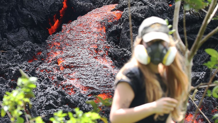 Lava flows at a new fissure in the aftermath of eruptions from the Kilauea volcano on Hawaii's Big Island as a local resident walks nearby after taking photos on May 12, 2018 in Pahoa, Hawaii.