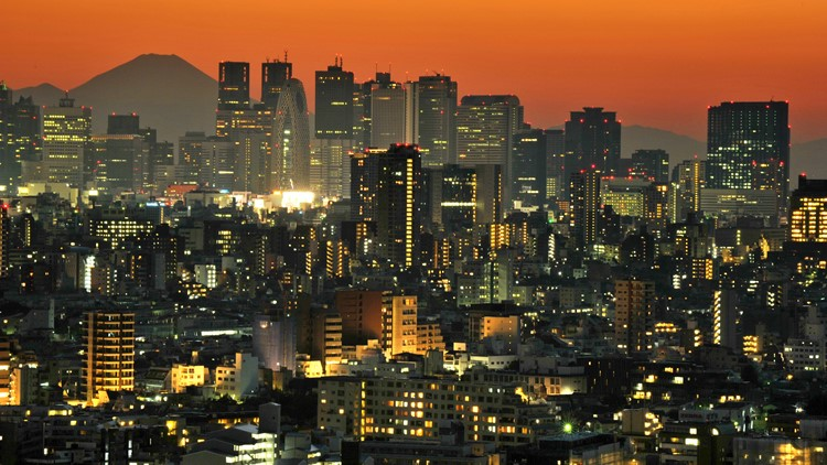 Japan's highest mountain Mount Fuji rises up behind the skyscrapers dotting the skyline of the Shinjuku area of Tokyo at sunset on 21 October, 2012.