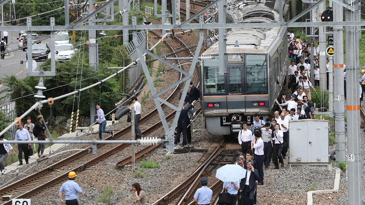 Passengers from a train walk along railroad tracks following an earthquake in Osaka on June 18, 2018. (STR/AFP/Getty Images)