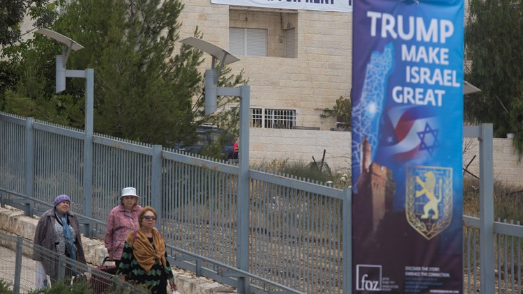 Israeli women walk next to a sign outside the US consulate that will act as the new US embassy in May 13, 2018 in Jerusalem, Israel.