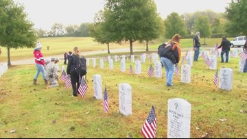 Volunteers place flags for Veterans Day
