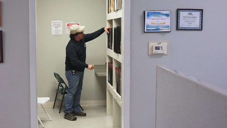 NamUs Director Todd Matthews searches through old newspaper archives at the Crossville Chronicle.