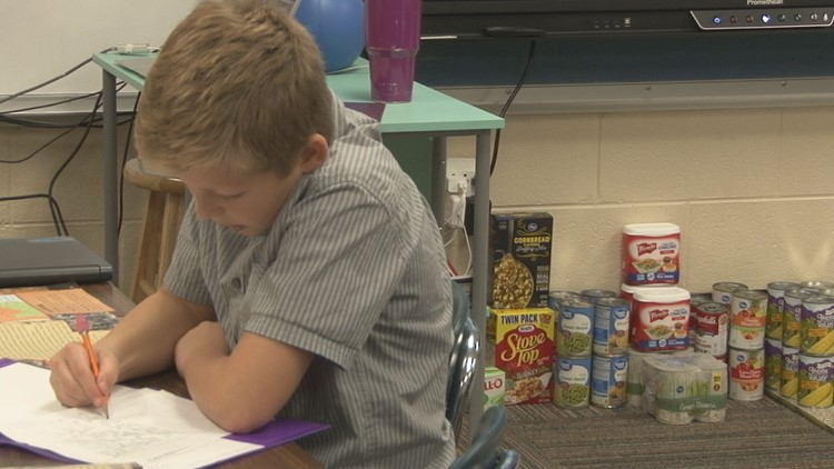 Alex Koloske participates in a canned food drive at his school