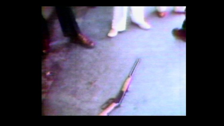 Bystanders gather around rifle used by Robert Patty